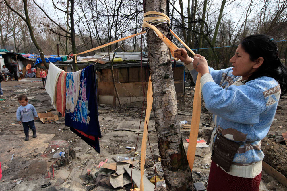 . A Roma woman hangs her laundry outside their shelter in an illegal camp in Lille, northern France, during International Roma Day on April 8, 2013.   REUTERS/Pascal Rossignol