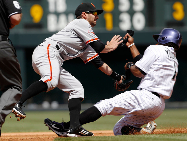 . San Francisco Giants second baseman Nick Noonan, left, tries to field the throw as Colorado Rockies\' Eric Young steals second base in the first inning of the MLB National League baseball game in Denver on Sunday, May 19, 2013. (AP Photo/David Zalubowski)