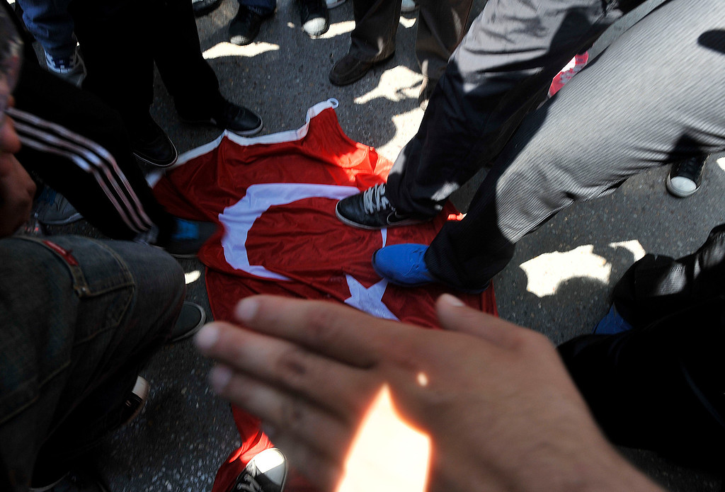 . Protesters walk over a Turkish flag during the annual rally to protest the mass killings of Armenians in Ottoman Turkey nearly a century ago in Thessaloniki, Greece on Wednesday April 24, 2013. About 250 protesters, mostly from Greek-Armenian groups, gathered outside the Turkish consulate. About 20 countries worldwide, including Greece, as well as the European parliament recognize the mass killings as an act of genocide, despite strong objections from Turkey. (AP Photo/Nikolas Giakoumidis)