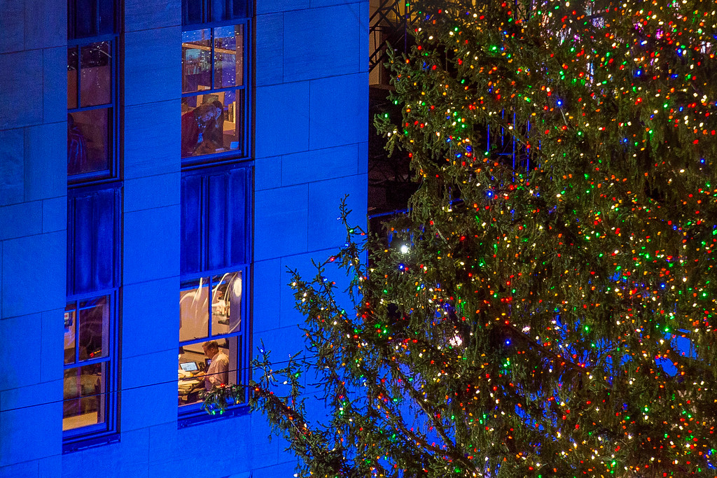. People watch as the Rockefeller Center Christmas tree stands lit at Rockefeller Center during the 85th annual Rockefeller Center Christmas tree lighting ceremony, Wednesday, Nov. 29, 2017, in New York. (AP Photo/Andres Kudacki)