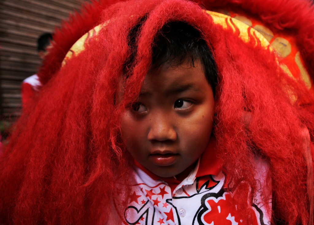 . An ethnic Chinese boy looks through a lion mask as he celebrates on the first day of lunar new year in Kolkata, India, Friday, Feb. 16, 2018. People in Asia and around the world are celebrating the Lunar New Year on Friday with festivals, parades and temple visits to ask for blessings. This year marks the year of the dog, one of the 12 animals in the Chinese astrological chart. (AP Photo/Bikas Das)