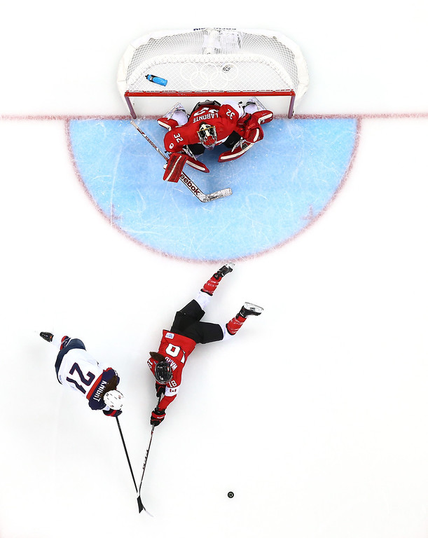 . Hilary Knight #21 of the United States goes for a loose puck as Catherine Ward #18 of Canada dives and Charline Labonte #32 tends net during the Women\'s Ice Hockey Preliminary Round Group A game on day five of the Sochi 2014 Winter Olympics at Shayba Arena on February 12, 2014 in Sochi, Russia.  (Photo by Martin Rose/Getty Images)