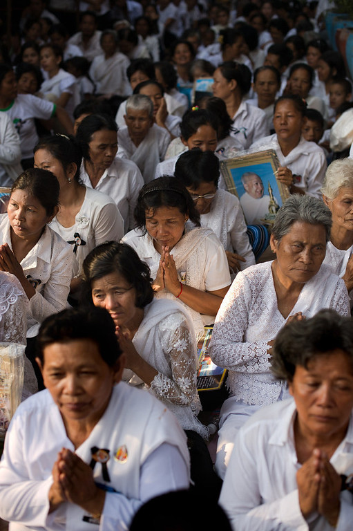 . Cambodian mourners sit and pray in a street in front of the crematorium where a coffin bearing the remains of Cambodia\'s late King Norodom Sihanouk is placed before his cremation, near the Royal Palace in Phnom Penh on February 4, 2013. Thousands of mourners massed in the Cambodian capital as the kingdom cremated its revered former King Norodom Sihanouk, who steered his country through six turbulent decades. AFP PHOTO/ Nicolas  ASFOURI/AFP/Getty Images