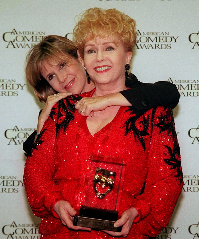 """. Debbie Reynolds is hugged by her daughter Carrie Fisher backstage of the 11th annual American Comedy Awards in Los Angeles Sunday, Feb. 9, 1997. Reynolds was awarded a Lifetime Achievement Award at the ceremony. Both women are currently appearing in films, Reynolds in \""""Mother,\"""" and Fisher is in the re-release of \""""Star Wars.\"""" (AP Photo/Rene Macura)"""