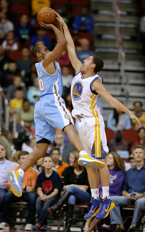 . Golden State Warriors guard Klay Thompson, right, blocks a shot by Denver Nuggets guard Arron Afflalo during the first half of a preseason NBA basketball game, Thursday, Oct. 16, 2014, in Des Moines, Iowa. (AP Photo/Charlie Neibergall)