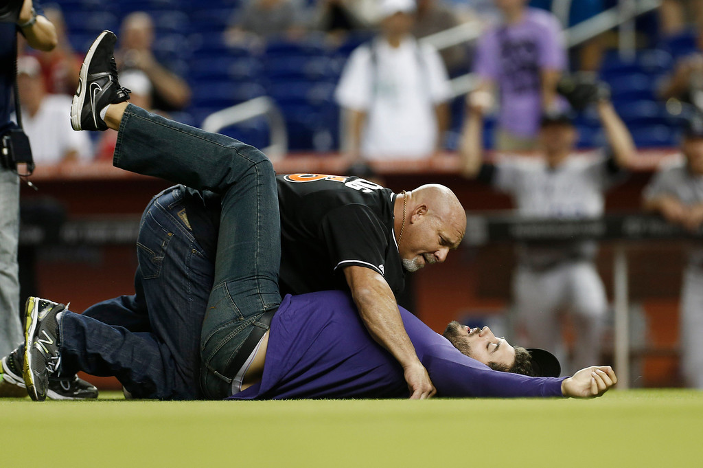 """. Professional wrestler Bill Goldberg, left, tackles a \""""bad guy\"""" on the field before a baseball game in Miami between the Colorado Rockies and Miami Marlins, Saturday, Aug. 24, 2013. (AP Photo/J Pat Carter)"""