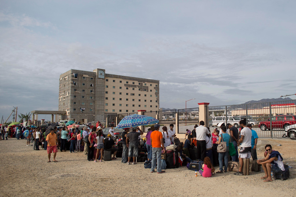 . Tourists wait to be evacuated, on the outskirts of the airport in San Jose de los Cabos, Mexico, Friday, Sept. 19, 2014. Officials estimated that as many as 30,000 travelers were stranded by Hurricane Odile, a monster Category 3 storm that roared over the resort area late Sunday. (AP Photo/Dario Lopez-Mills)