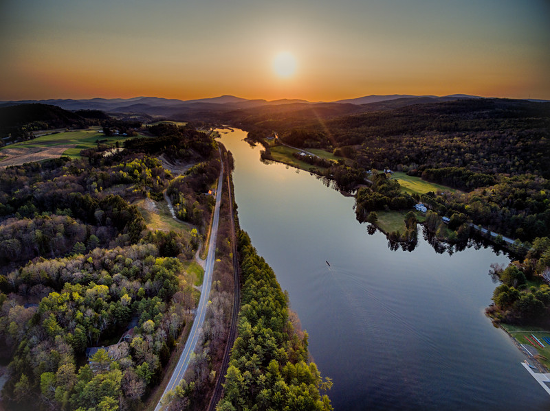 Sunrise over the Connecticut River Valley just north of Hanover, NH and Norwich, VT. The high scool crew team making their way upstream for practice.