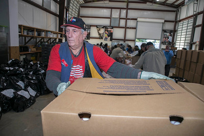 Bishop Blesses Christmas Food Boxes and Gifts at Catholic Charities