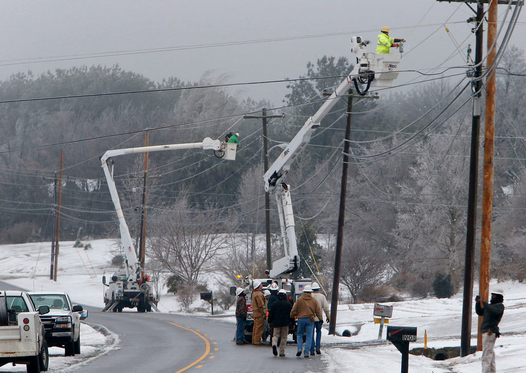 . Fort Payne Improvement Authority workers work on lines that had become heavy with ice and were being blown around by high winds, Wednesday, Feb. 12, 2014, in Dog Town, Ala. Trees and limbs began snapping under the weight of a coat of ice in east Alabama Wednesday, blocking roads during a winter storm that forecasters said could leave as much as a foot of snow in the Tennessee Valley. (AP Photo/Hal Yeager)