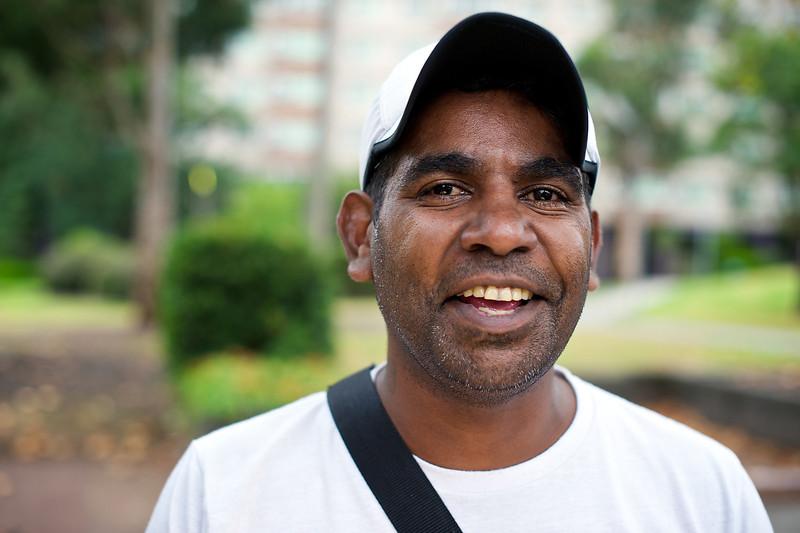 Young Aboriginal Man smiling, outdoors, urban location