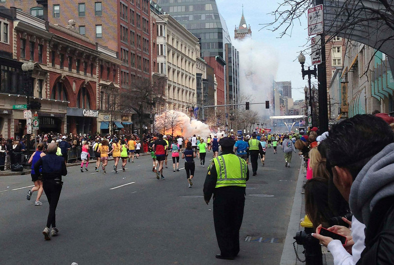 . Runners continue to run towards the finish line of the Boston Marathon as an explosion erupts near the finish line of the race in this photo exclusively licensed to Reuters by photographer Dan Lampariello after he took the photo in Boston, Massachusetts, April 15, 2013. Two simultaneous explosions ripped through the crowd at the finish line of the Boston Marathon on Monday, killing at least two people and injuring dozens on a day when tens of thousands of people pack the streets to watch the world famous race.  REUTERS/Dan Lampariello