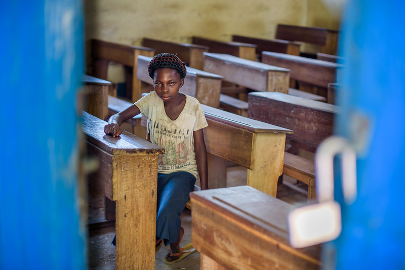 """Marie Ngalula, 14 yr-old girl, wishes her family could afford to send her to school. Photos of her in a classroom at St. Celestin school, where she would attend if she was still in school.  School Marie's father laments his inability to send her back to school. """"Marie is intelligent,"""" he says. """"She could help me very much someday.  I'd like to send her back to school but I can't afford it. I'd like if she could further her studies even as far as university so that she can help me take care of her brothers and sisters someday.""""  Marie and her friends often play on the grass in front of the school they can't afford to go to.  Marie lives with her father, Alexandre Tshimanga, her mother, Ntumba Kalombo Antoinette and her brothers and sisters: 1-Kena Tshimanga, 12 2-Kankonde Moise, 10 3-Munamba Angel, 8 4-Musungayi Andre, 6 5-Mubuyi Tshimanga, 4  Marie lives in a small village outside of Kananga, Democratic Republic of Congo, DRC, called Tubuluku, which means antelopes (plural). Her house is a two-room hut with a thatched roof.  Handful of wooden chairs are the only furniture. She lives here with an extended family of 13.  Home Life Marie is a bright girl but there is a sadness in her eyes. Marie's mother is in the nearby health clinic with a staph infection that has caused a huge abscess on her right side. It has become very serious. As a result, Marie has assumed many of the household duties.  She's forced, at 14, to assume the duties of an adult. Besides cooking for her brothers and sisters, she sweeps up the husks from palm nuts she crushes. She saves the husks to use as kindling for the fire. Marie and her siblings all sleep together in one room, huddled together for warmth and cover by an old and torn mosquito net.   Hunger Marie's family is desperately hungry in the days we visit them. Because her mother is sick and his father spends his days tending to her in the clinic, there is no money for food. Because there isn't any cassava flour and cornmeal to make fufu,"""