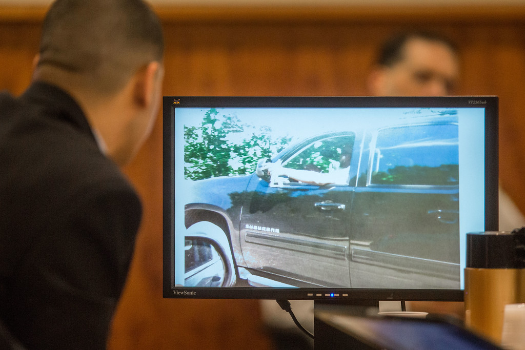 . Former New England Patriots tight end Aaron Hernandez, left, looks closely at a photo of Odin Lloyd during his murder trial at Bristol County Superior Court Monday March 2, 2015, in Fall River, Mass. Hernandez is accused of the June 2013 killing of Odin Lloyd. (AP Photo/The Boston Globe, Aram Boghosian, Pool)