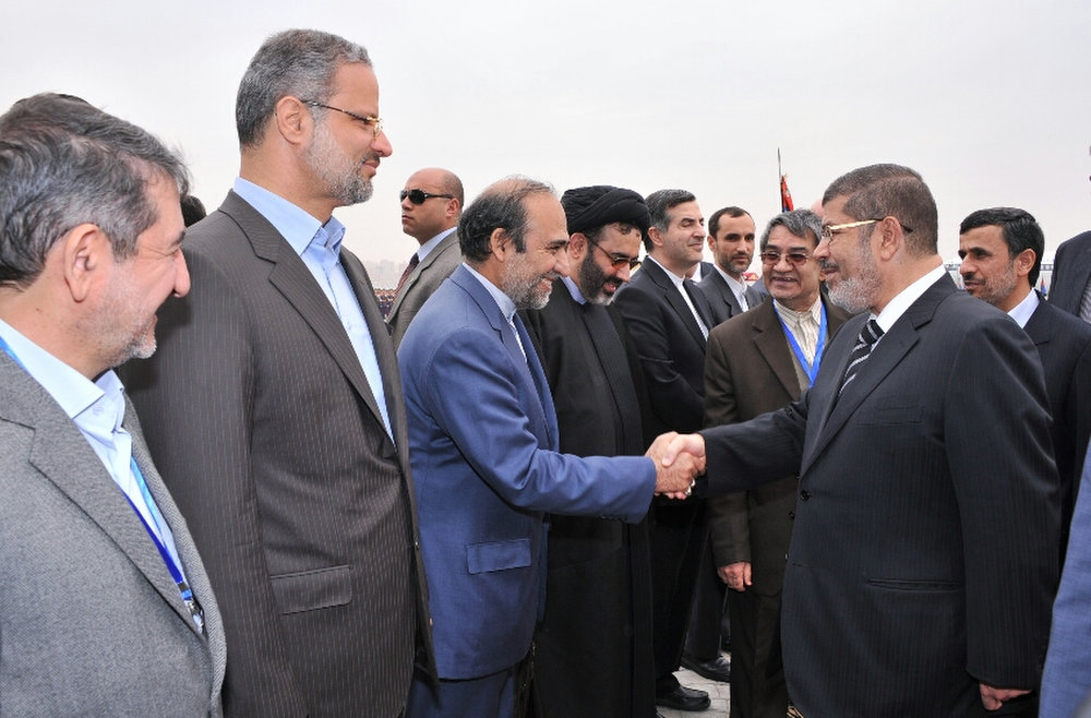 Description of . In this image released by the Egyptian Presidency, Iran's President Mahmoud Ahmadinejad, right, looks on as and Egyptian President Mohammed Morsi, second right, shakes hands with the Iranian delegation at the airport in Cairo, Egypt, Tuesday, Feb. 5, 2013. Ahmadinejad arrived in Cairo on Tuesday for the first visit by an Iranian leader in more than three decades, marking a historic departure from years of frigid ties between the two regional heavyweights.(AP Photo/Egyptian Presidency)