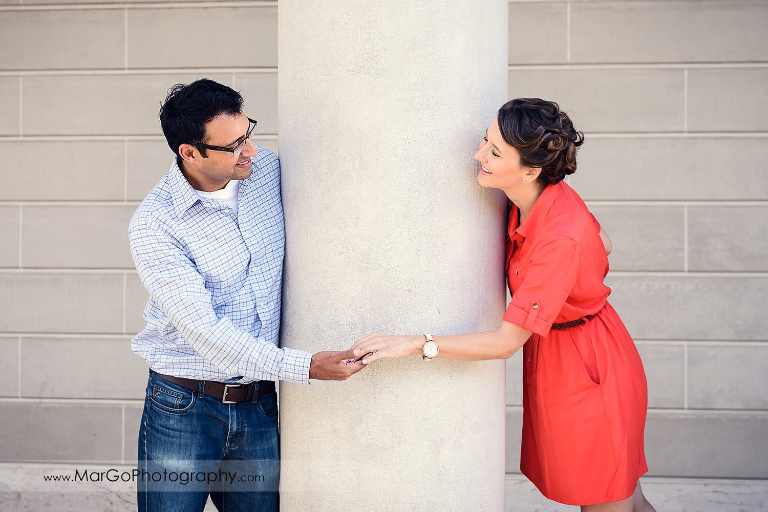 man in blue shirt and woman in red dress holding hands infront of white column during engagement session at San Francisco Legion of Honor