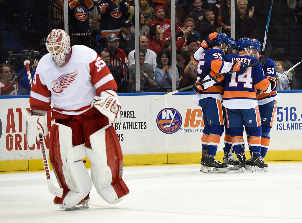 . New York Islanders defenseman Johnny Boychuk (55), defenseman Johnny Boychuk (14), center Casey Cizikas (53) and right wing Cal Clutterbuck (15) celebrate Clutterbuck\'s goal as Detroit Red Wings goalie Jimmy Howard (35) skates away in the second period of an NHL hockey game on Sunday, March 29, 2015, in Uniondale, N.Y. (AP Photo/Kathy Kmonicek)