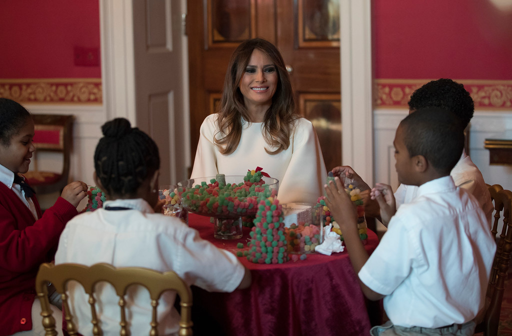 """. First lady Melania Trump visits with children in the Red Room working on holiday treats among the 2017 holiday decorations with the theme \""""Time-Honored Traditions\"""" at the White House in Washington, Monday, Nov. 27, 2017. The First Lady honored 200 years of holiday traditions at the White House. (AP Photo/Carolyn Kaster)"""