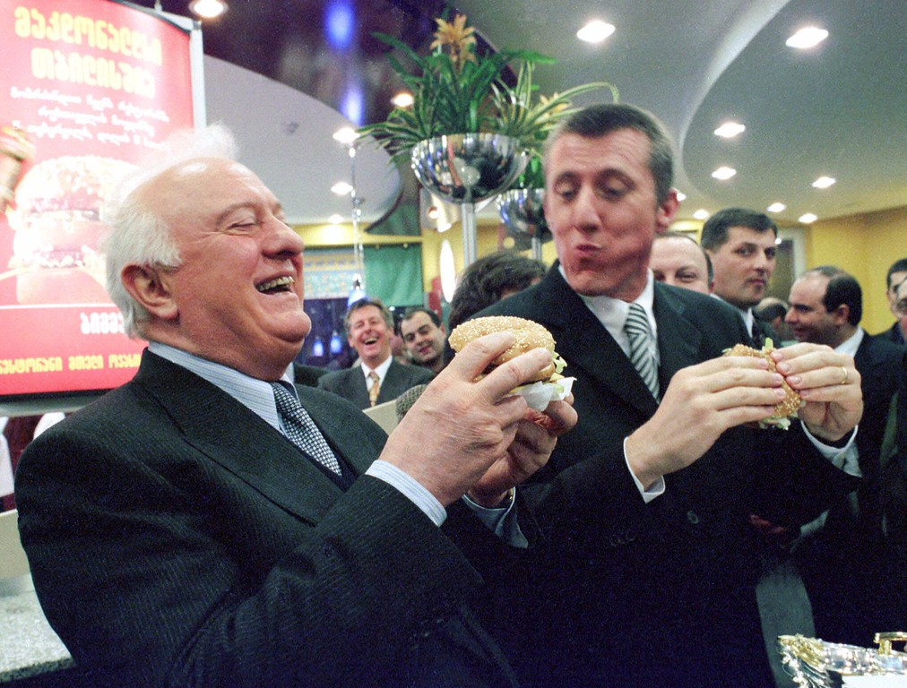 . Georgian President Eduard Shevardnadze laughs while tasting a Big Mac while Andreas Hacker, right, McDonald\'s corporate vice president, looks on at a presentation ceremony of McDonald\'s fast food restaraunt in Tbilisi, Thursday, Feb. 4, 1999. This is the first McDonald\'s opened in Georgia. (AP Photo/Shakh Aivazov)