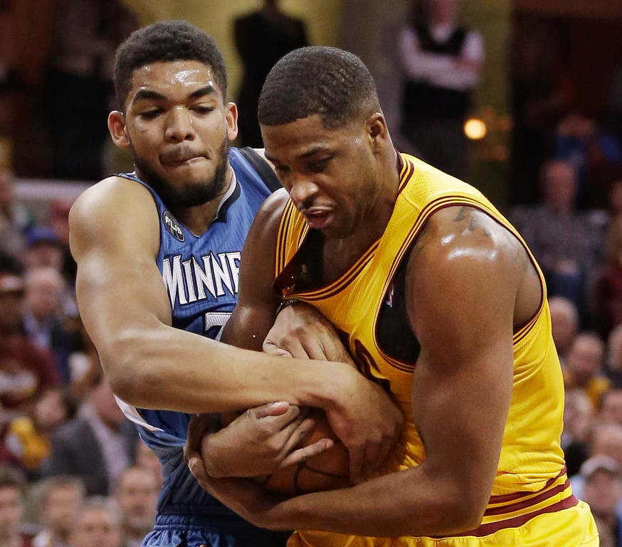 . Minnesota Timberwolves\' Karl-Anthony Towns, left, and Cleveland Cavaliers\' Tristan Thompson, from Canada, battle for the ball in the first half of an NBA basketball game Monday, Jan. 25, 2016, in Cleveland. (AP Photo/Tony Dejak)