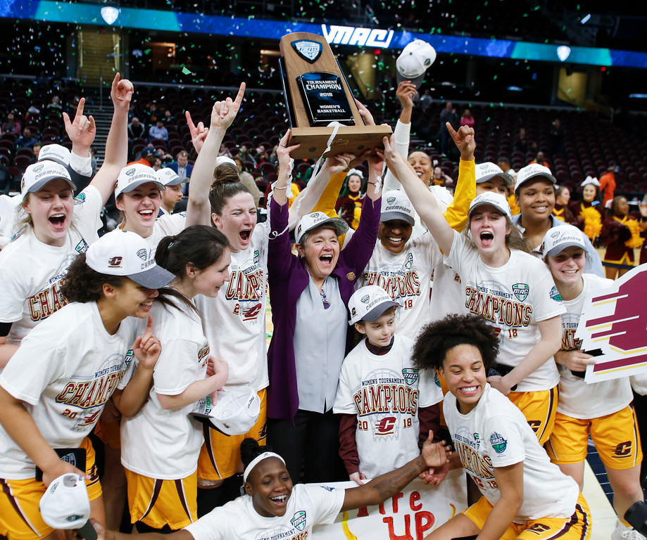 . Central Michigan head coach Sue Guevara holds up the trophy after defeating Buffalo 96-91 in an NCAA college basketball game during the championship of the Mid-American Conference tournament Saturday, March 10, 2018, in Cleveland. (AP Photo/Ron Schwane)