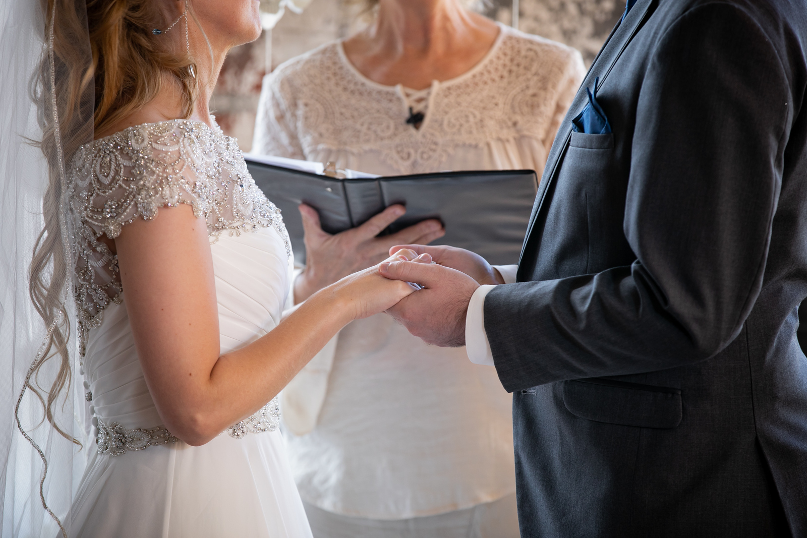 bride wearing a princess cut wedding dress holding hands with her groom wearing a dark grey suit in front of their officiant at the altar