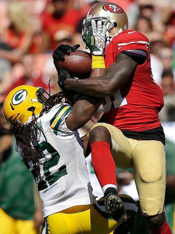 . San Francisco 49ers wide receiver Anquan Boldin catches a pass over Green Bay Packers defensive back Jerron McMillian (22) during the second quarter of an NFL football game in San Francisco, Sunday, Sept. 8, 2013. (AP Photo/Marcio Jose Sanchez)