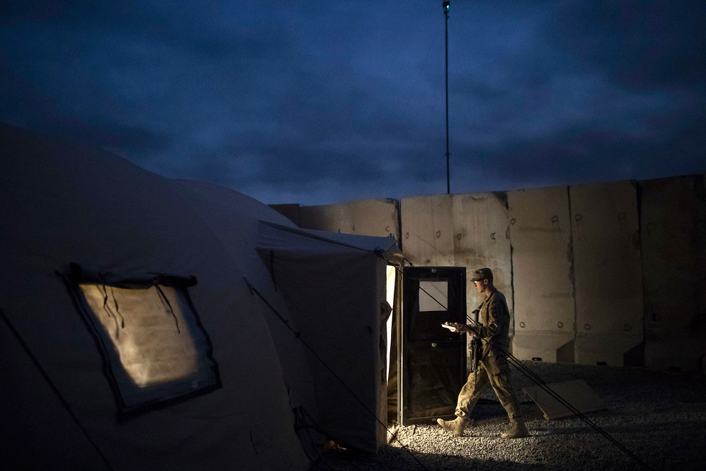 . A U.S. Army soldier walks to a tent with his Thanksgiving dinner at a coalition air base in Qayara south of Mosul, Iraq, Thursday, Nov. 24, 2016. (AP Photo/Felipe Dana)