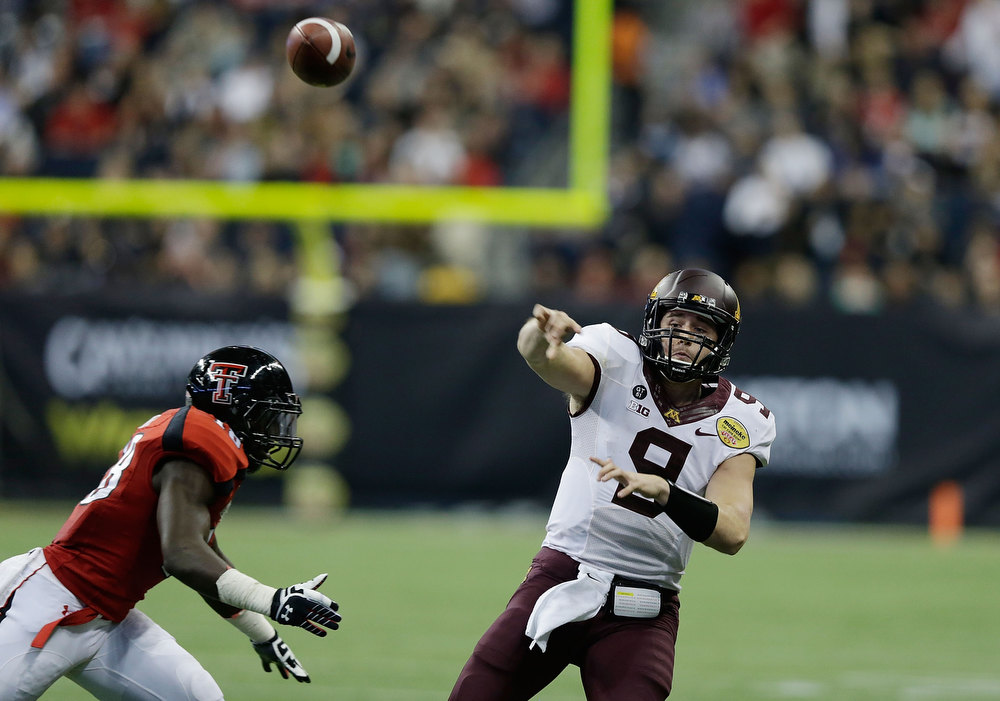 Description of . Phillip Nelson #9 of Minnesota looks to pass as he is pressured by Micah Awe #18 of Texas Tech during the Meineke Car Care of Texas Bowl at Reliant Stadium on December 28, 2012 in Houston, Texas.  (Photo by Scott Halleran/Getty Images)