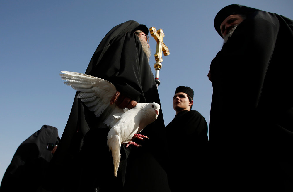 . A Greek Orthodox priest holds a dove before a ceremony at the baptismal site known as Qasr el-Yahud on the banks of the Jordan River near the West Bank city of Jericho January 18, 2013. Over a thousand Orthodox Christians flocked to the Jordan River to celebrate the feast of the Epiphany at the traditional site where it is believed John the Baptist baptised Jesus. REUTERS/Baz Ratner