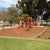 open plan timber house cubby and bench seat in mulch with brick edging