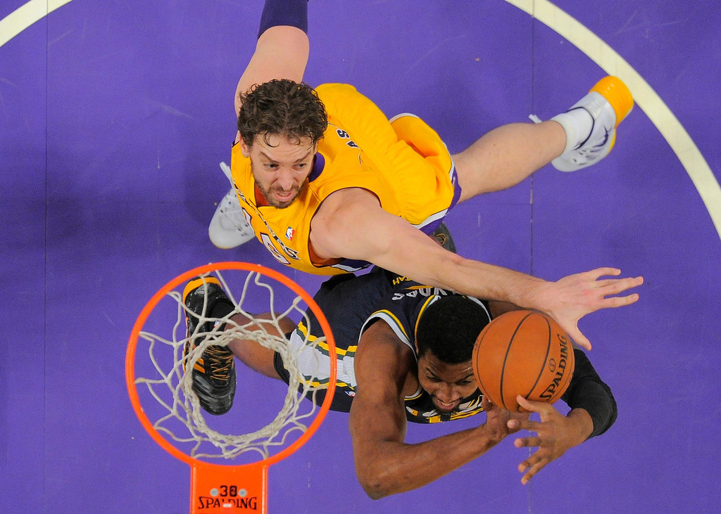 . Utah Jazz forward Derrick Favors, right, puts up a shot as Los Angeles Lakers center Pau Gasol, of Spain, defends during the first half of an NBA basketball game, Friday, Jan. 3, 2014, in Los Angeles. (AP Photo/Mark J. Terrill)
