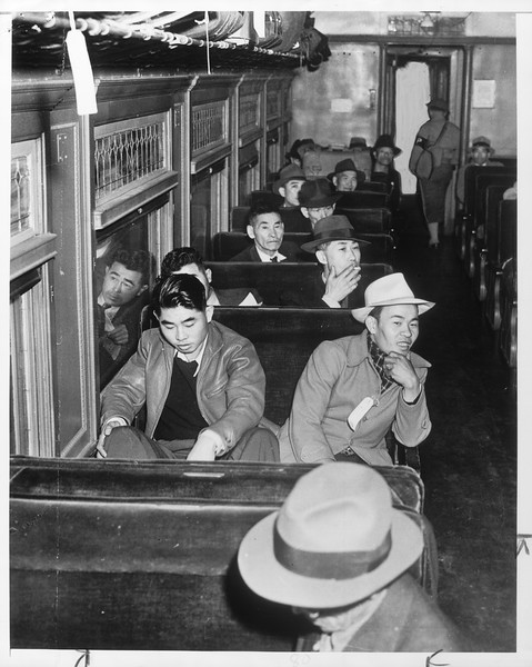 """""""Happy, for the most part, were Japs who formed vanguard of evacuees.  Here are some of the 500 on train.""""--caption on photograph"""