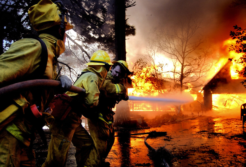 . Ten years ago this month the arson caused Old Fire, fanned by Santa Ana winds burned thousands of acres, destroyed hundreds of homes and caused six deaths. The fire burned homes in San Bernardino, Highland, Cedar Glen, Crestline, Running Springs and Lake Arrowhead and forced the evacuation of thousand of residents. Fire fighters try to reach a house on fire near Crestline, on Sunday October 26, 2003 on the second day of the Old Fire. (Staff file photo/The Sun)