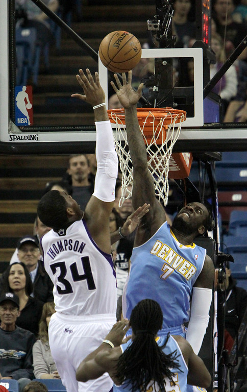. Denver Nuggets forward J.J. Hickson, right, tries to block the shot of Sacramento Kings forward Jason Thompson during the first quarter of an NBA basketball game in Sacramento, Calif., Sunday, Jan. 26, 2014. (AP Photo/Rich Pedroncelli)