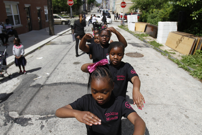 . Members of a local drill team prepare to perform in a neighborhood procession near the site of an abandoned home in the impoverished Mantua section Philadelphia on Saturday, May 31, 2014. The cultural and memorial project called �Funeral for a Home� celebrated the dilapidated row house\'s colorful life before it was knocked down. Organizers from Temple University said it was an effort to commemorate neighborhood history in a city where about 600 houses are torn down each year and 25,000 others sit vacant. (AP Photo/Jessica Kourkounis)