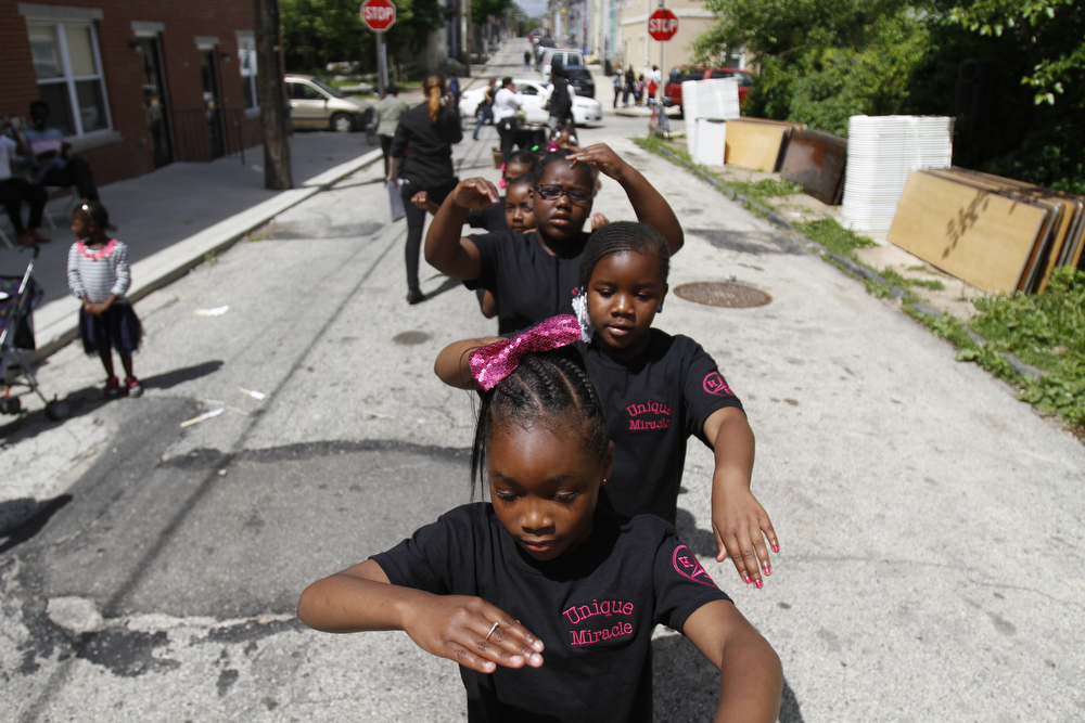 """Description of . Members of a local drill team prepare to perform in a neighborhood procession near the site of an abandoned home in the impoverished Mantua section Philadelphia on Saturday, May 31, 2014. The cultural and memorial project called """"Funeral for a Home"""" celebrated the dilapidated row house's colorful life before it was knocked down. Organizers from Temple University said it was an effort to commemorate neighborhood history in a city where about 600 houses are torn down each year and 25,000 others sit vacant. (AP Photo/Jessica Kourkounis)"""