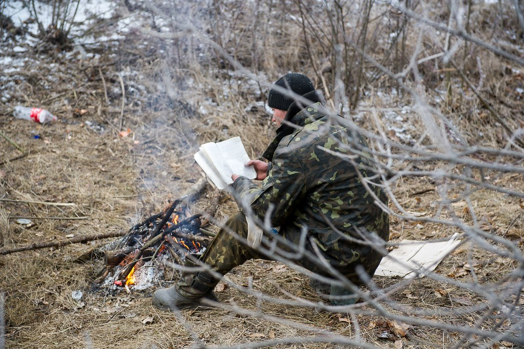 . A Ukrainian serviceman reads a book as he warms himself by a camp fire in Svitlodarsk, approaching Debaltseve on February 15, 2015. A ceasefire in Ukraine was cautiously observed by both sides, despite accusations by Kiev and the US that Russia had fuelled a final push by rebels to gain territory before the deadline. Ukrainian President Petro Poroshenko ordered troops to abide by the truce from midnight (2200 GMT), in line with a deal reached in Minsk earlier this week with the leaders of Russia, Germany and France. VOLODYMYR SHUVAYEV/AFP/Getty Images