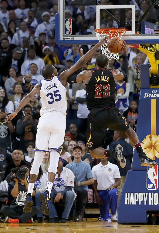 . Golden State Warriors forward Kevin Durant (35) blocks Cleveland Cavaliers forward LeBron James (23) during the second half of an NBA basketball game in Oakland, Calif., Monday, Dec. 25, 2017. The Warriors won 99-92. (AP Photo/Tony Avelar)
