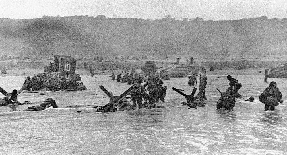 Description of . In this June 6, 1944 file picture, some of the first assault troops to hit the Normandy, France beachhead take cover behind enemy obstacles to fire on German forces as others follow the first tanks plunging through the water towards the German-held shore during World War II. (AP Photo)