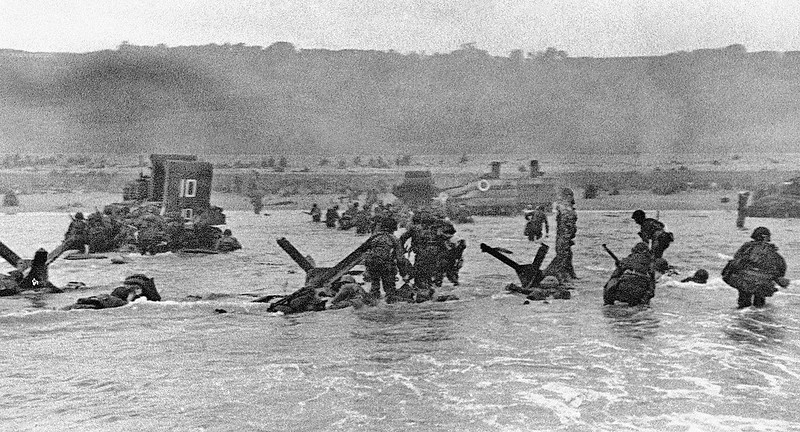 . In this June 6, 1944 file picture, some of the first assault troops to hit the Normandy, France beachhead take cover behind enemy obstacles to fire on German forces as others follow the first tanks plunging through the water towards the German-held shore during World War II. (AP Photo)