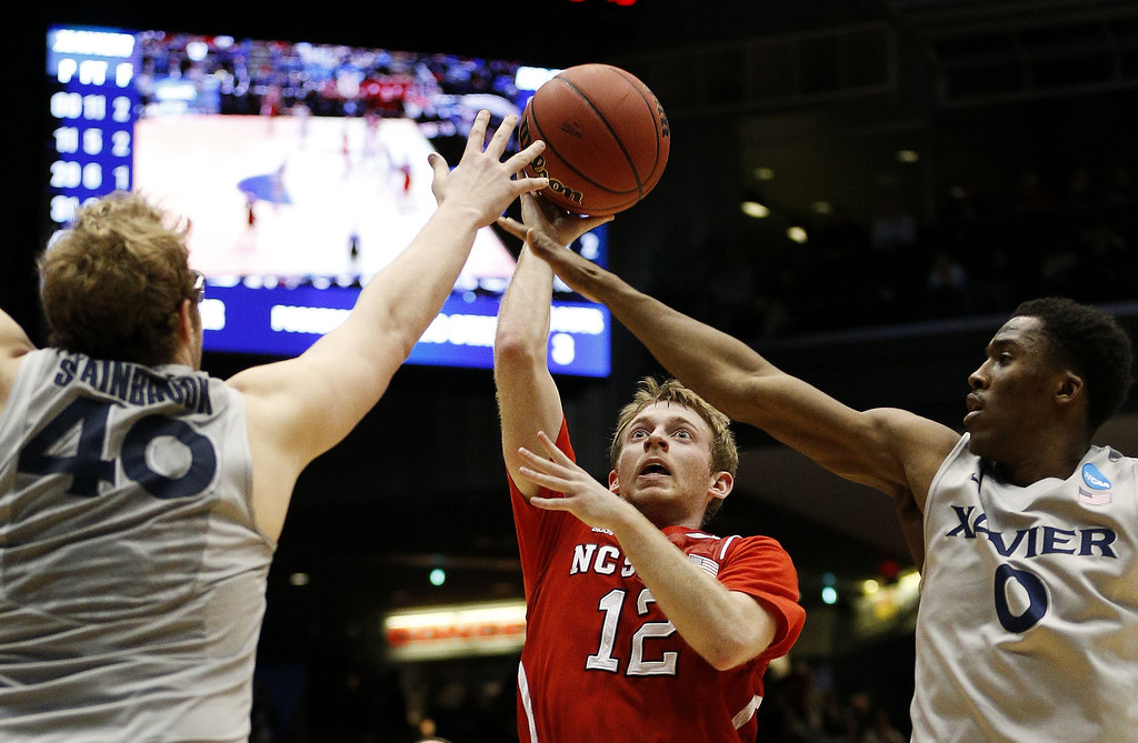 . Tyler Lewis #12 of the North Carolina State Wolfpack goes up between Matt Stainbrook #40 and Semaj Christon #0 of the Xavier Musketeers in the second half during the first round of the 2014 NCAA Men\'s Basketball Tournament at at University of Dayton Arena on March 18, 2014 in Dayton, Ohio.  (Photo by Gregory Shamus/Getty Images)