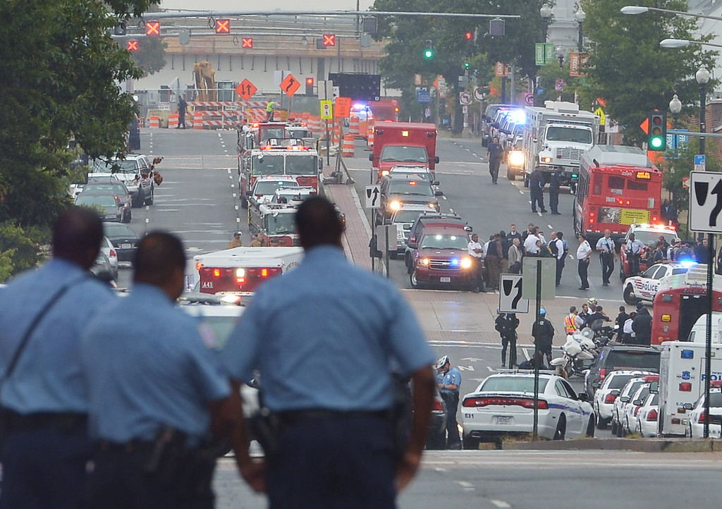 . A general view shows police and first responder activity on M Street, SE near the Washington Navy Yard on September 16, 2013 in Washington, DC.  An unidentified gunman opened fire at the US Navy Yard in Washington on Monday and wounded several people including two police officers, officials reported. Police and FBI agents descended on the area in force as helicopters buzzed overhead, amid reports the shooter was armed with an assault rifle and was on the loose in the complex. A Washington DC police officer and another law enforcement officer had been shot while the gunman had allegedly barricaded himself in a room in a headquarters building, the Washington Post and other media reported. At one point a police helicopter hovering over the complex lowered a man down by rope into the compound. Police blocked off intersections around the Navy Yard as military troops in uniform stood guard at street corners.   MANDEL NGAN/AFP/Getty Images