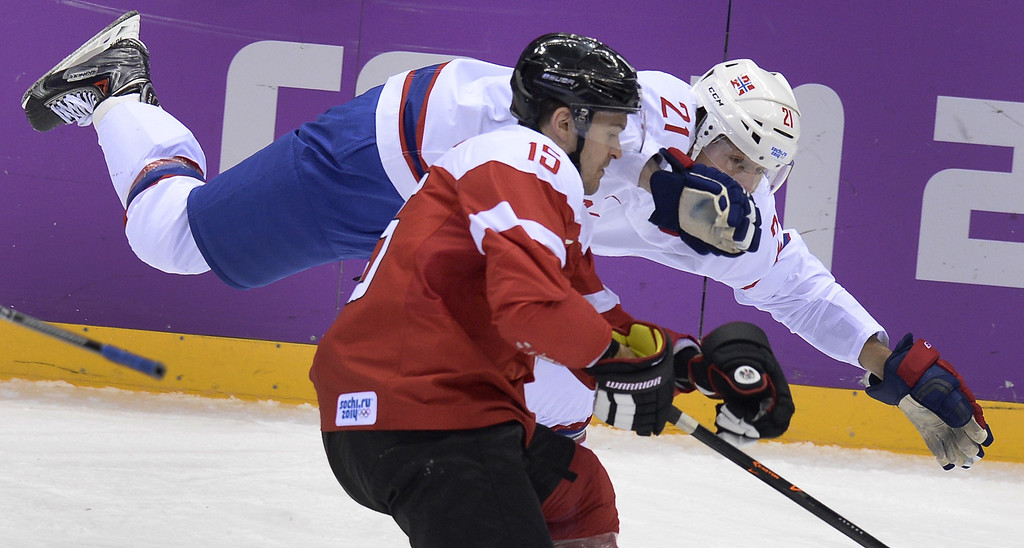 . Austria\'s Manuel Latusa (front) vies with Norway\'s Morten Ask during the Men\'s Ice Hockey Group B match at the Bolshoy Ice Dome during the Sochi Winter Olympics on February 16, 2014 in Sochi.  ALEXANDER NEMENOV/AFP/Getty Images