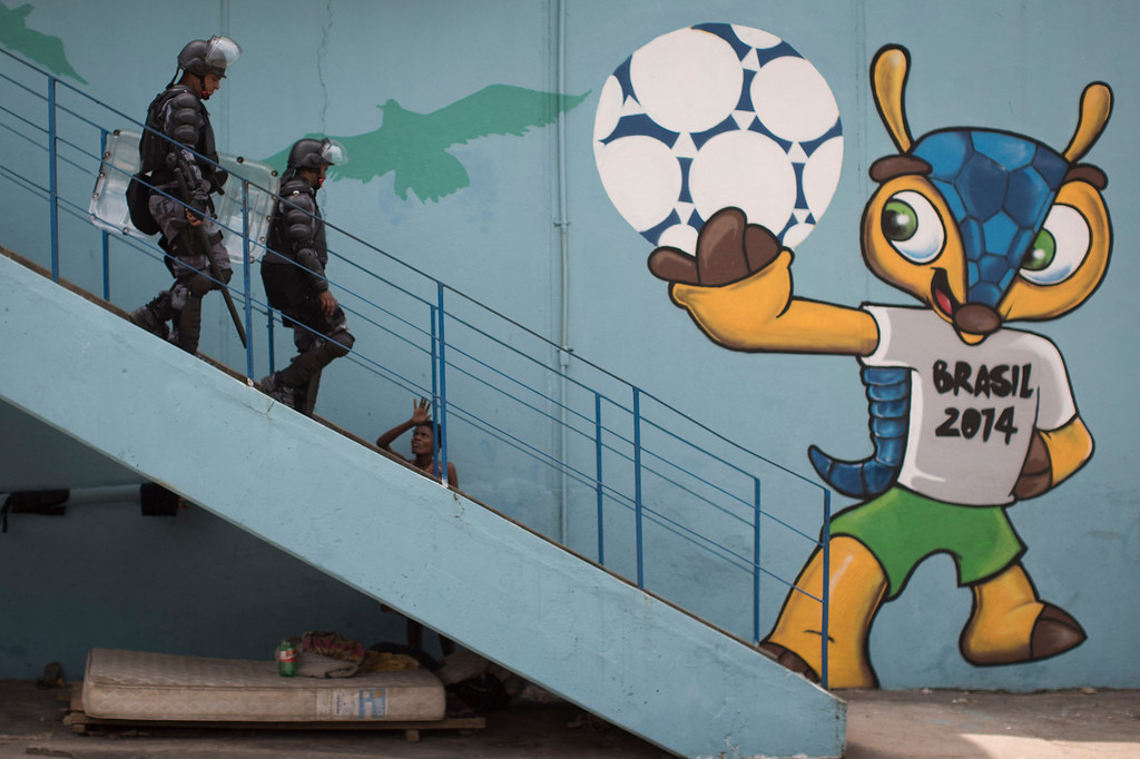 . Riot police walk next to a mural of the mascot for the 2014 World Cup soccer tournament, called Fuleco, near the Maracana stadium, after evicting Indians from the nearby old Indian Museum in Rio de Janeiro, Friday, March 22, 2013. Police in riot gear invaded an old Indian museum complex Friday and pulled out a few dozen indigenous people who for months resisted eviction from the building, which will be razed as part of World Cup preparations next to the legendary Maracana football stadium. (AP Photo/Felipe Dana)