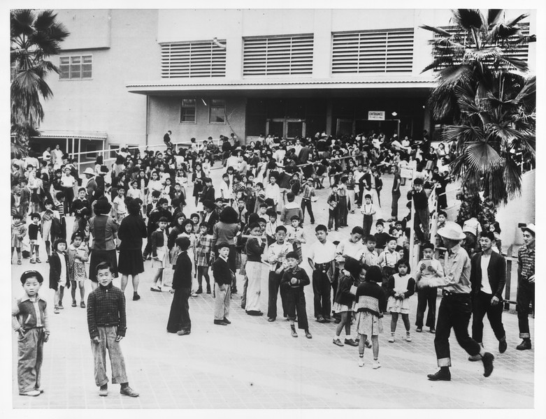 """""""Awaiting the School Opening -- Japanese school children wait for school to open.  It's held in grandstand at Santa Anita Assembly Center.""""--caption on photograph"""
