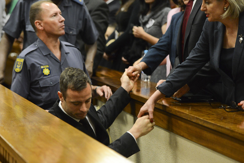 . Paralympian Oscar Pistorius holds the hands of family members as he is taken down to the holding cells after being sentenced to five years imprisonment for the culpable homicide killing of his girlfriend Reeva Steenkamp at the high court in Pretoria, on October 21, 2014. AFP PHOTO/POOL / HERMAN VERWEY/AFP/Getty Images