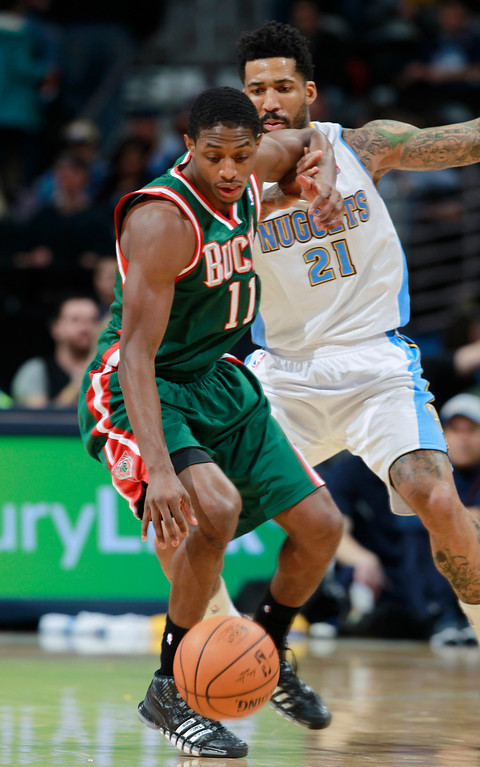 . Milwaukee Bucks guard Brandon Knight, ront, picks up a loose ball as Denver Nuggets forward Wilson Chandler covers in the fourth quarter of the Nuggets\' 110-100 victory in an NBA basketball game in Denver on Wednesday, Feb. 5, 2014. (AP Photo/David Zalubowski)