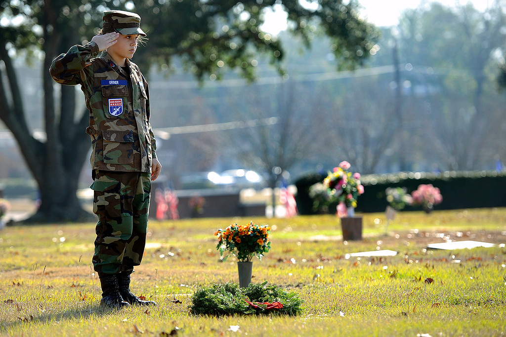 . Cadet Senior Airman Avery Griner, right, salutes a veteran\'s grave after placing her tribute Saturday, Dec. 13, 2014, during Wreaths Across American Day at Sunset Memorial Park in Nacogdoches, Texas. The program started in 1992 at Arlington National Cemetery in Virginia and has spread to almost 550 locations nationally to honor deceased veterans and service members listed as missing in action during the holiday season. (AP Photo/The Daily Sentinel, Andrew D. Brosig)