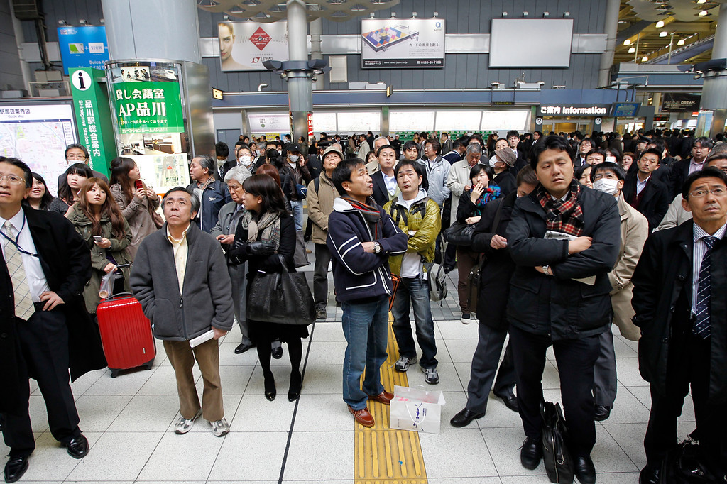 . Train passengers wait at Tokyo\'s Shinagawa station to get first-hand information on train service which was halted following a very strong earthquake on Friday March 11, 2011. Japan says the death toll in the massive earthquake has risen to five. The quake unleashed a 13-foot (4-meter) tsunami that swept boats, cars, buildings and tons of debris miles inland. (AP Photo/Hiro Komae)